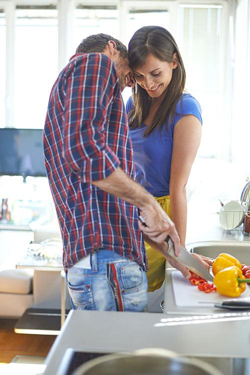 Premarital couple looking happy in the kitchen.