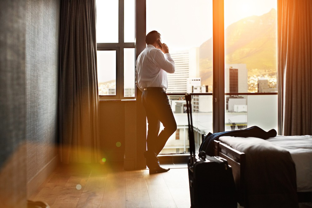 Man in hotel room on cell phone talking to his counselor